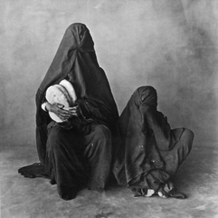 Two women, wearing black, with bread. Morocco 1971.,Irving Penn