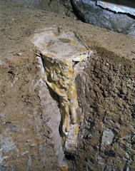 Detail of Object #17 in its clay matrix beneath the basement floor, undergoing excavation. This solid cone of beeswax was cast on site in The Grange basement. It contains a deer\'s shoulder bone, a human braid and woven fabric.,Iris Hussler