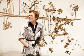 Exhibiting artist Kristi Lippire in front of her installation, Hanging Garden, Kristi Lippire