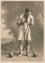 Studio photograph of Houdini in white trunks and chains, Harry Houdini
