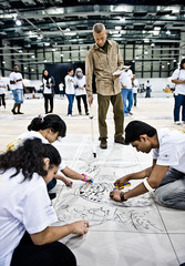 Cai Guo-Qiang and volunteers working on gunpowder drawing Frieze, Doha, Qatar , Cai Guo-Qiang