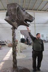 Ai Weiwei reaching for the Dog Zodiac Head at the bronze foundry in Chengdu, China,