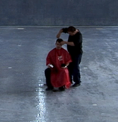Still from Ordos 100, of Ai Weiwei cutting hair,