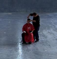 Still from Ordos 100, of Ai Weiwei cutting hair,