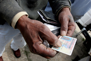 Tyrone Williams_0384 Lower Ninth Ward, New Orleans, LA.; April 2007; Tyrone Williams, a construction worker takes out his temporary New Jersey id. He evacuated to Newark, NJ when Hurricane Katrina hit and worked temporarily selling Christmas trees. Yet he, Collette V. Fournier