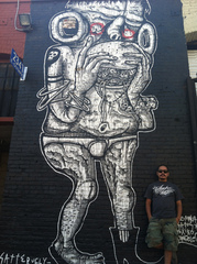 Satterugly in front of his mural in DTLA,Satterugly