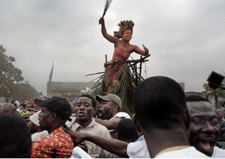 A traditional dancer and crowd salute Jean-Pierre Bemba as he walks to a rally from the airport, Kinshasa , Guy Tillim