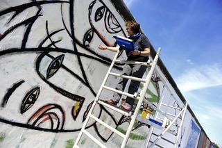 Renovating Berlin Wall painting, Margaret Hunter