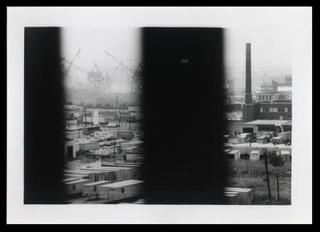 Untitled [Port Newark-Elizabeth Marine Terminal, with trucks and loading cranes in distance, seen through bridge slats], George Segal